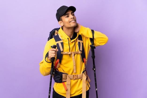 Uomo afroamericano con lo zaino e pali di trekking sopra la parete isolata che pensa un'idea