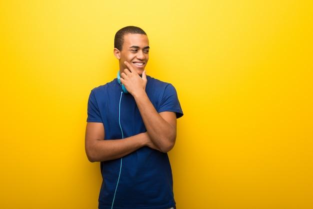 Uomo afroamericano con t-shirt blu su sfondo giallo alla ricerca