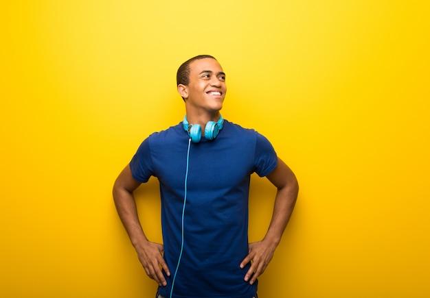 Uomo afroamericano con t-shirt blu su sfondo giallo in posa con le braccia in anca e ridendo