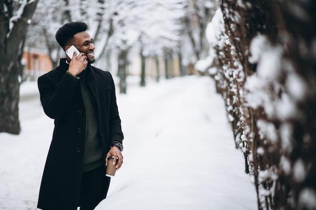 Uomo afroamericano con telefono e caffè in inverno all'aperto