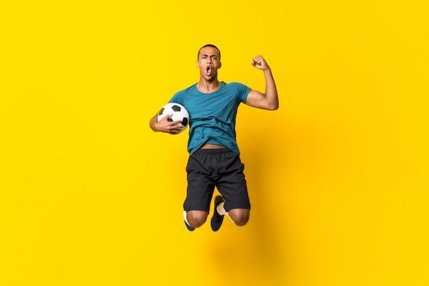 Uomo afroamericano del giocatore di football americano sopra fondo giallo isolato