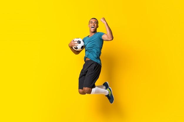 Uomo afroamericano del giocatore di football americano sopra giallo isolato