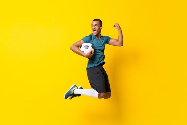 Uomo afroamericano del giocatore di football americano sopra la parete gialla isolata