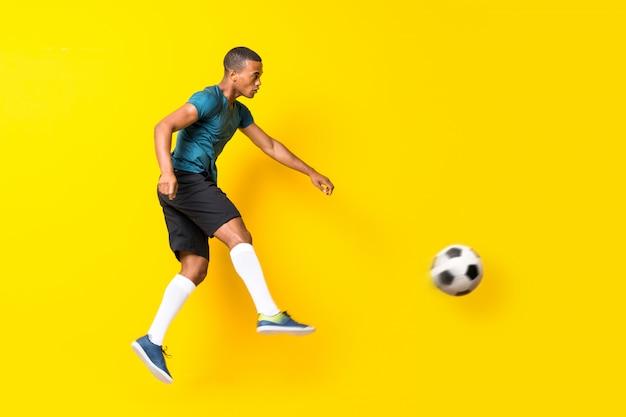 Uomo afroamericano del giocatore di football americano su giallo