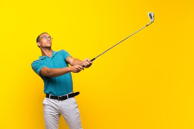 Uomo afroamericano del giocatore di giocatore di golf sopra giallo isolato