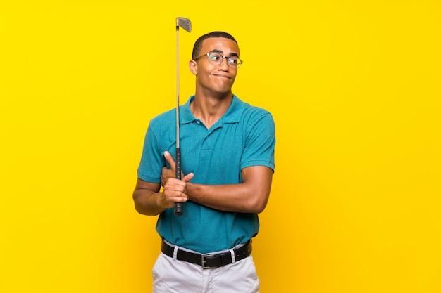 Uomo afroamericano del giocatore di golf che fa gesto di dubbi mentre sollevando le spalle