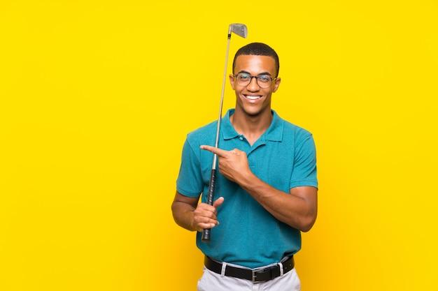 Uomo afroamericano del giocatore di golfista che indica il lato per presentare un prodotto