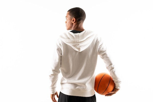Uomo afroamericano del giocatore di pallacanestro sopra fondo bianco isolato