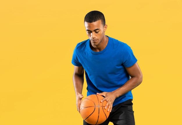 Uomo afroamericano del giocatore di pallacanestro sopra fondo giallo isolato
