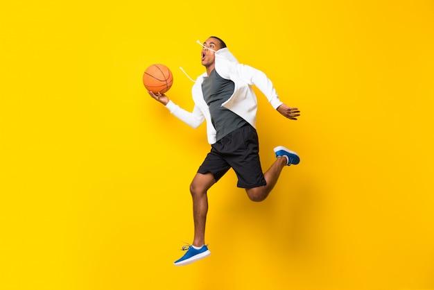 Uomo afroamericano del giocatore di pallacanestro sopra giallo isolato