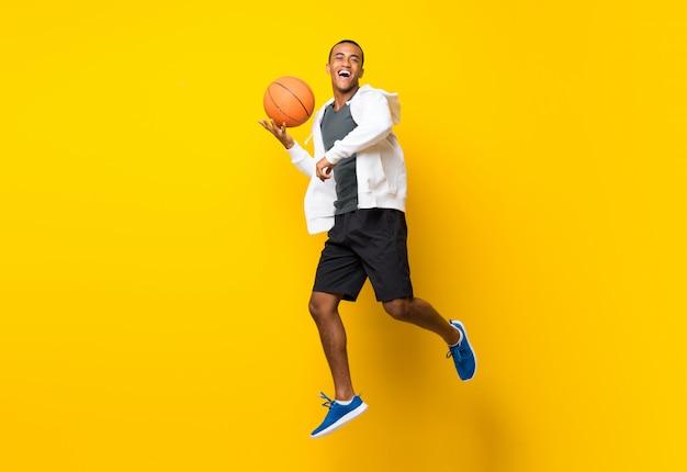 Uomo afroamericano del giocatore di pallacanestro su giallo
