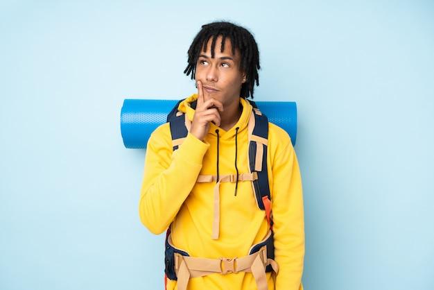 Uomo afroamericano del giovane alpinista con un grande zaino isolato su una parete blu che pensa un'idea