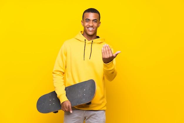 Uomo afroamericano del pattinatore che invita a venire con la mano. felice che tu sia venuto