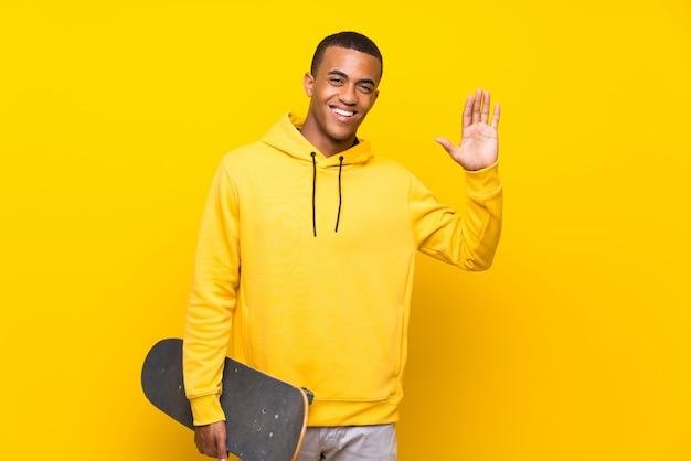 Uomo afroamericano del pattinatore che saluta con la mano con l'espressione felice