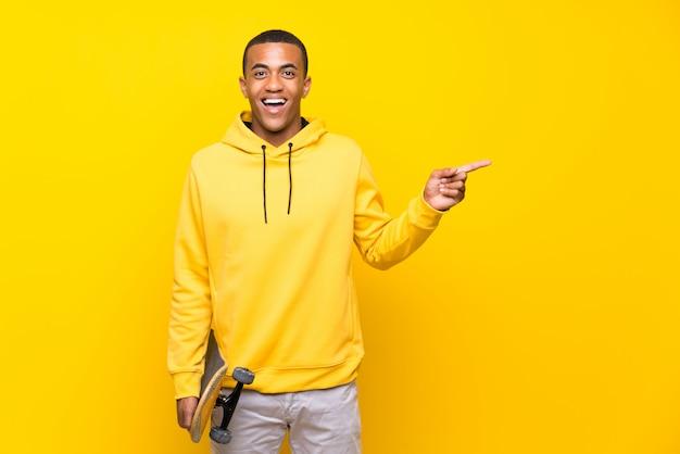 Uomo afroamericano del pattinatore sorpreso e puntando il dito verso il lato