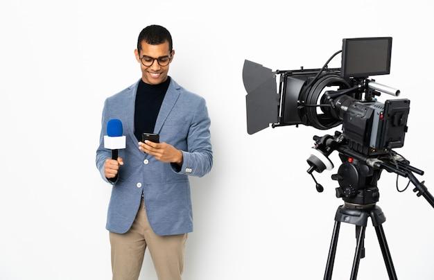 Uomo afroamericano del reporter che tiene un microfono e che riferisce le notizie sopra la parete bianca isolata che invia un messaggio con il cellulare
