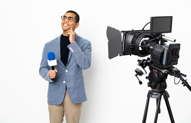 Uomo afroamericano del reporter che tiene un microfono e che riferisce le notizie sopra la parete bianca isolata che pensa un'idea mentre guardando su