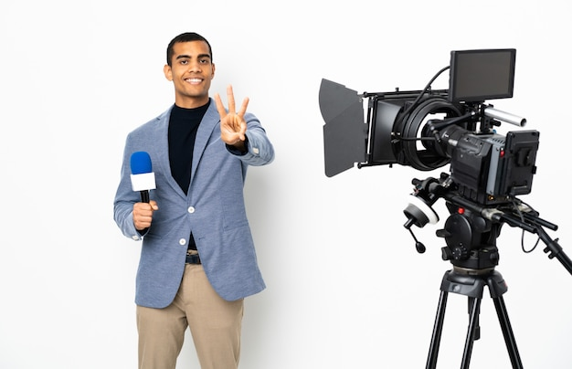 Uomo afroamericano del reporter che tiene un microfono e che riferisce le notizie sopra la parete bianca isolata felice e che conta tre con le dita