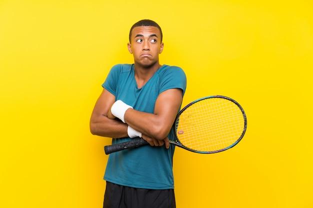 Uomo afroamericano del tennis che fa gesto di dubbi mentre sollevando le spalle