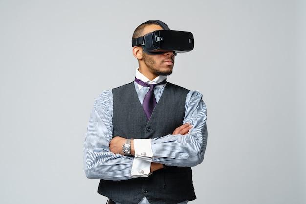 Uomo afroamericano di affari che usando una cuffia avricolare di realtà virtuale vr