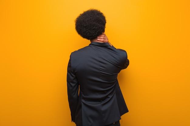 Uomo afroamericano di giovani affari sopra una parete arancio da dietro pensando a qualcosa