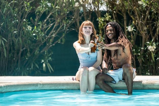 Uomo afroamericano e donna bianca che tostano con le bottiglie di birra sul bordo di uno stagno.