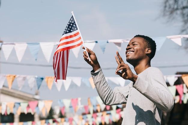 Uomo afroamericano felice che fluttua la bandiera di usa