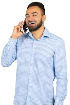 Uomo afroamericano felice che per mezzo di un telefono cellulare