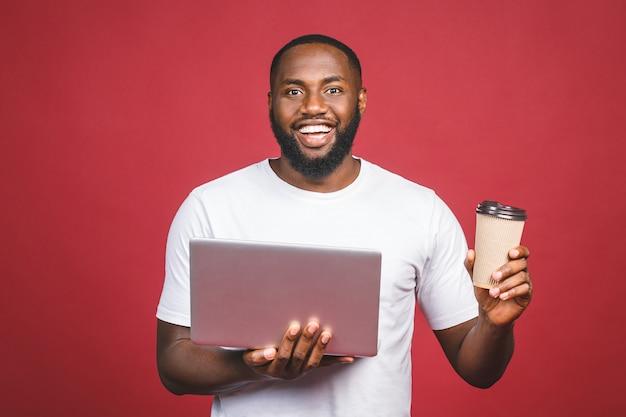Uomo afroamericano felice emozionante con lo schermo di computer, il caffè o il tè, celebrante la vittoria isolata sopra fondo rosso.