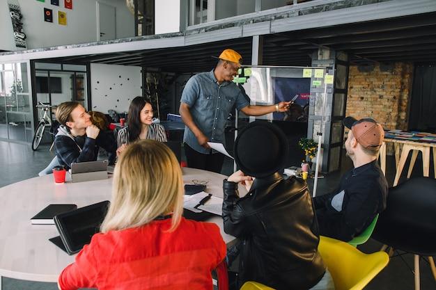 Uomo afroamericano in abbigliamento casual in piedi vicino alla parete dell'ufficio di vetro con punti finanziari, spiegando le strategie di pianificazione e di business ai colleghi, soluzioni creative sulla sessione di brainstorming