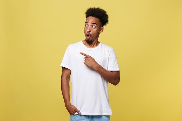 Uomo afroamericano in camicia bianca casuale che ha eccitato sguardo