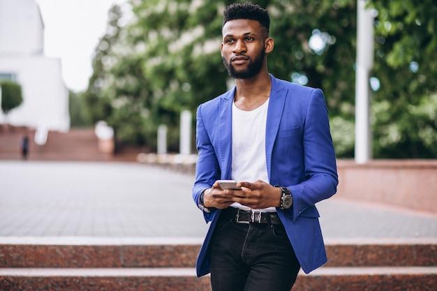 Uomo afroamericano in giacca blu utilizzando il telefono