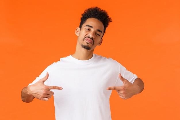 Uomo afroamericano sfrontato e sicuro di sé, che si comporta in modo disinvolto e sfacciato, indicandosi orgoglioso, orgoglioso in piedi arancione, in mostra, facendo impressione, indossando una maglietta bianca