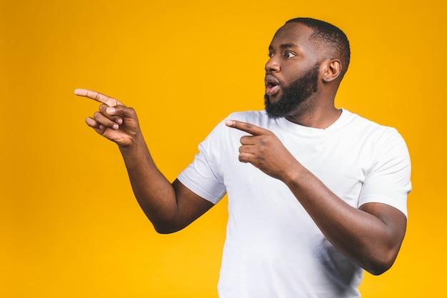 Uomo afroamericano sopra la parete isolata stupita mentre presentando con la mano e indicando con il dito.