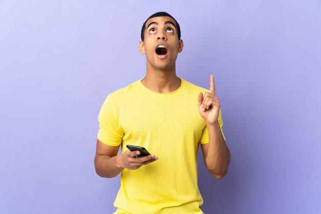 Uomo afroamericano sopra la parete porpora isolata facendo uso del telefono cellulare che indica con il dito indice una grande idea