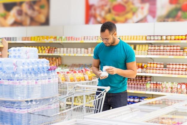 Uomo afroamericano sorridente che prende i prodotti dal congelatore