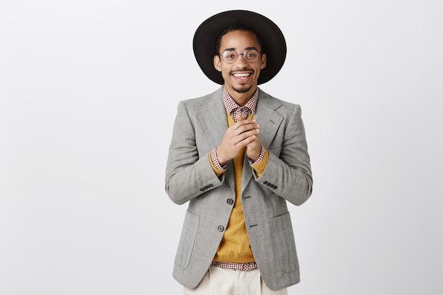 Uomo afroamericano sorridente grato bello che tiene le mani insieme e che guarda con apprezzamento
