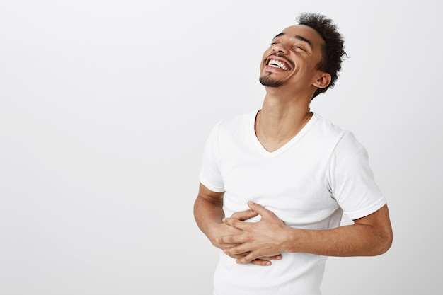 Uomo afroamericano spensierato che ride e sorride, ascolta uno scherzo divertente