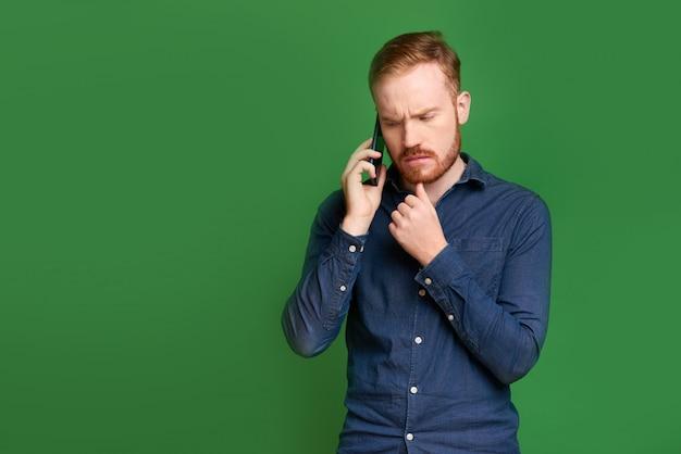Uomo aggrottante le sopracciglia che parla sul telefono