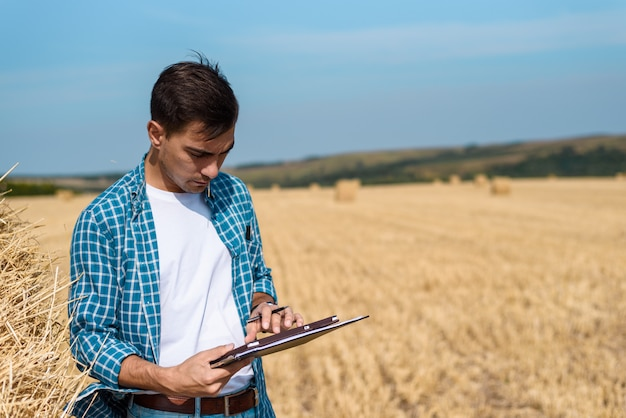 Uomo agricoltore con tavoletta in mano, jeans e camicia in campo, raccolta, fienagione