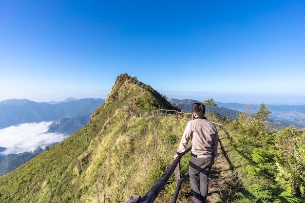 Uomo al di un percorso sulla cima di una montagna