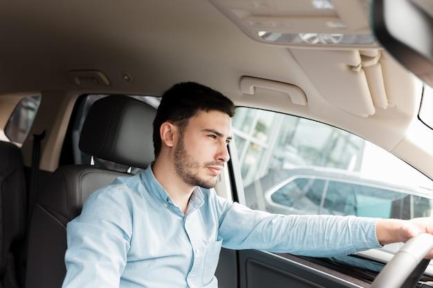 Uomo alla guida di un'auto costosa