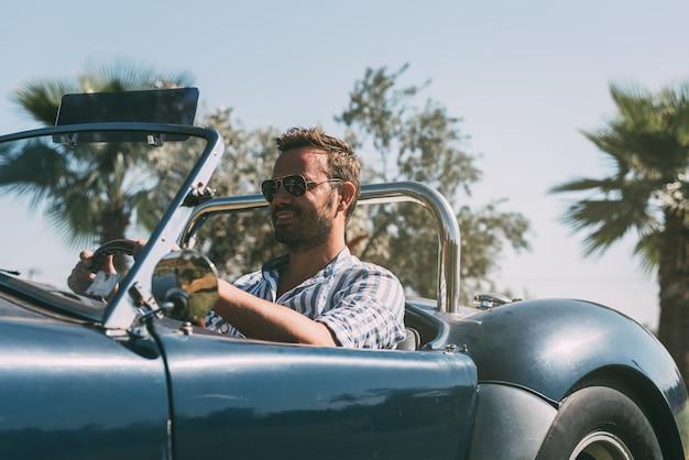 Uomo alla guida di un'auto d'epoca convertibile