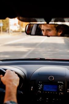 Uomo alla guida di un automobile visto attraverso il retrovisore