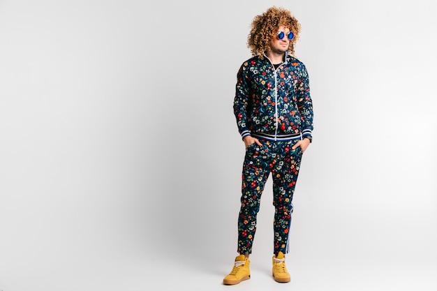 Uomo alla moda adulto in tuta sportiva alla moda con motivo a fiori, scarpe da ginnastica gialle in piedi con le mani in tasca sul muro bianco. maschio sicuro impressionante in ritratto degli occhiali da sole