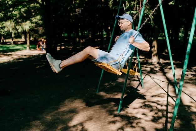 Uomo alla moda adulto in vetri che guidano oscillazione nel parco della città di estate.