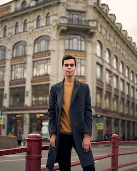 Uomo alla moda bello alla moda, bruna in elegante cappotto grigio, si trova sulla strada