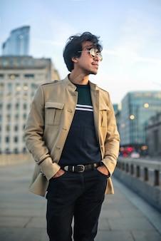 Uomo alla moda bello che cammina nella via al tramonto