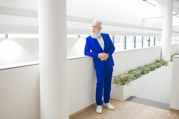 Uomo alla moda bello sul business center. uomo d'affari che sta sul fondo neutrale dell'ufficio, uomo sicuro maturo in vestito blu.