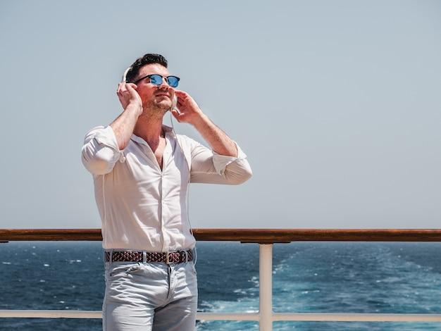 Uomo alla moda che ascolta la musica in cuffie bianche